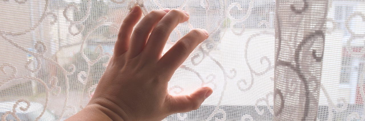woman's hand over a curtain on a window looking out over the street