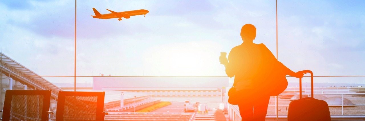 silhouette of traveler with suitcase waiting in airport