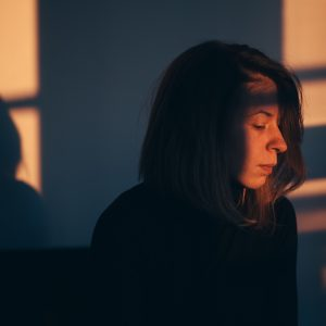 A woman sitting alone and sad in window light
