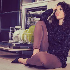 woman sitting on kitchen floor next to dishwasher