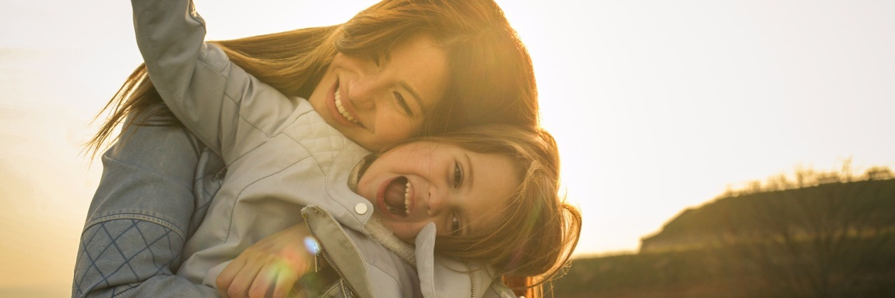 mother hugging her daughter outdoors