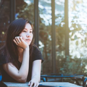 young woman sitting at cafe contemplating depressed