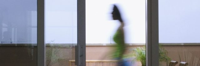 A woman walking past a glass sliding door