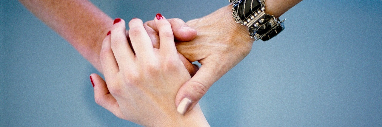 Three people holding hands