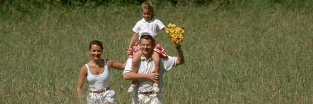 Family walking in a field on a sunny day.