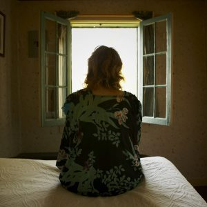 woman sitting on her bed and looking out the window
