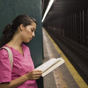 Nurse waiting for subway reading book