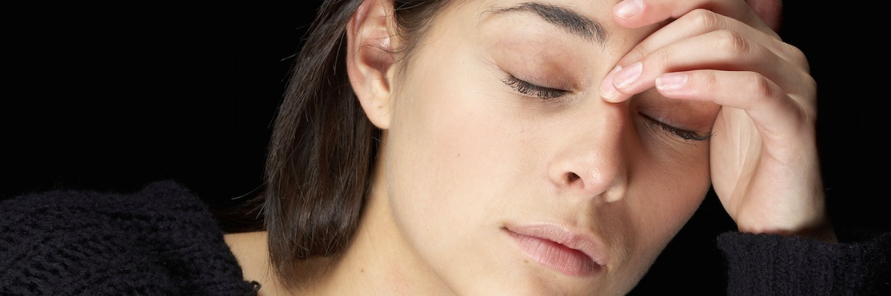 Woman with a headache, eyes closed, hand across forehead