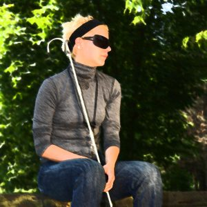 Blind woman sitting on a park bench on a sunny day.