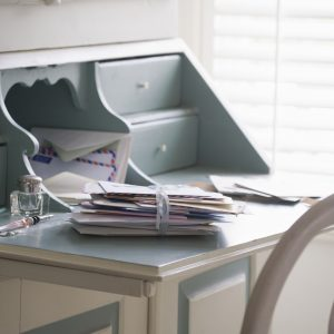 Letters tied with ribbon on writing desk.