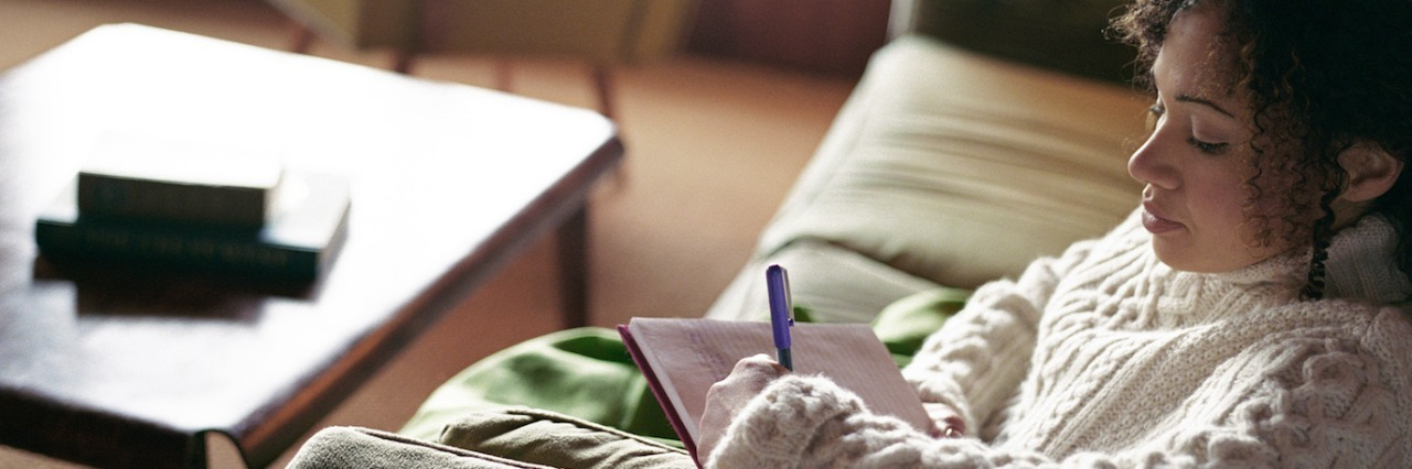 Woman sitting on sofa, writing letter