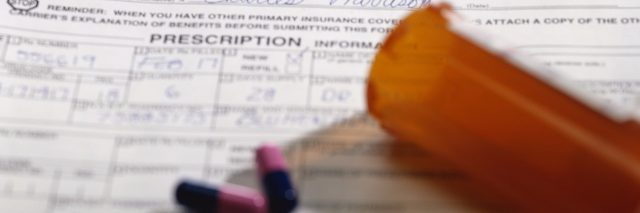 insurance forms with bottle of pills spilled on top