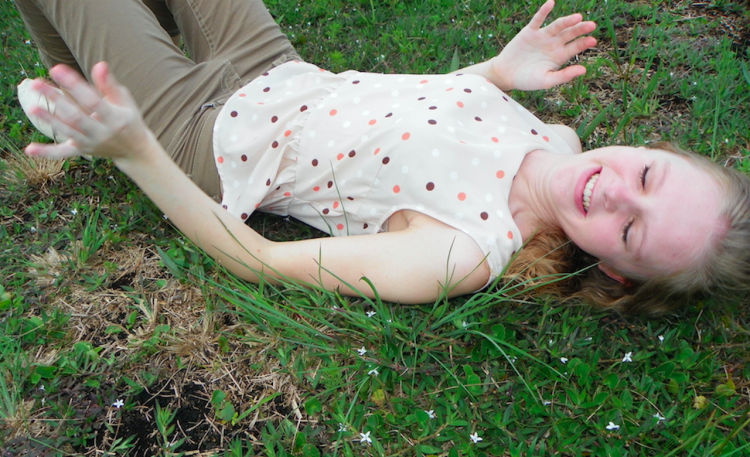 teenage girl lying in the grass and laughing