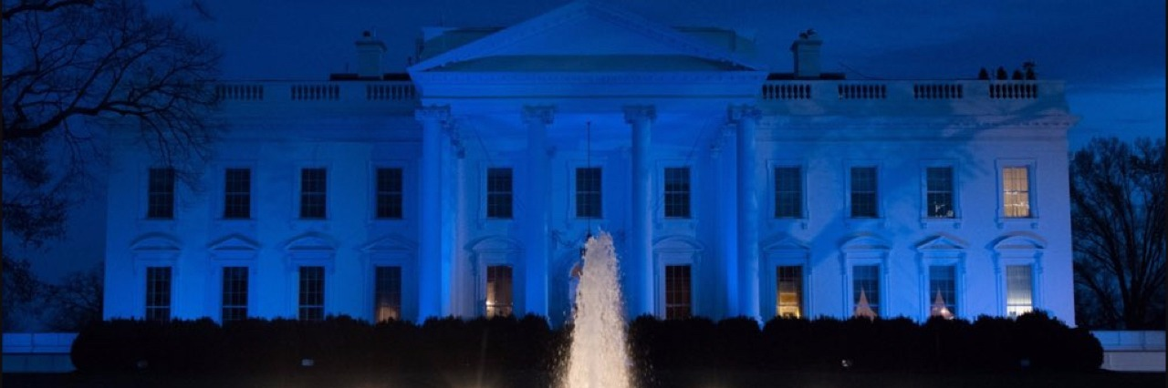 Photo of the White House lit blue.