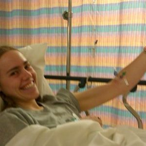young woman smiling in hospital bed with tubes attached to her arm
