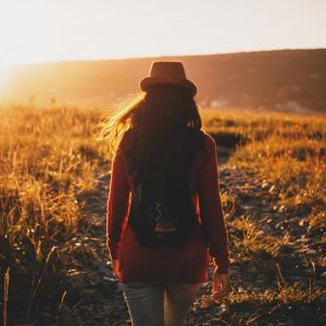 Woman walking through field at sunset