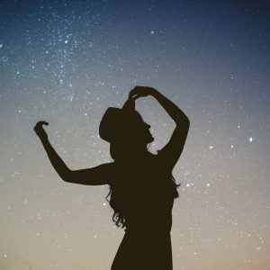 woman silhouetted against starry night sky