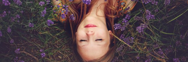 woman at peace lying on her back in purple flowers