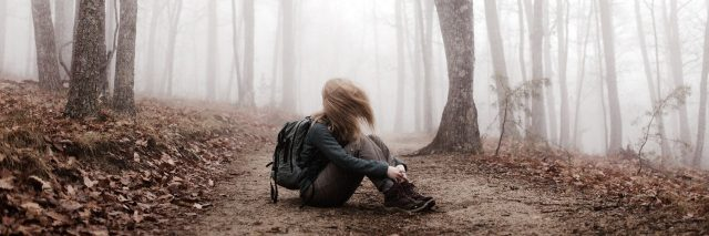 girl sitting alone in forest fog with hair covering face