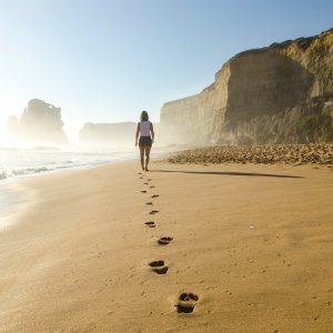 beach footprints in sand leading to woman in distance