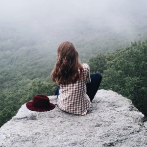 young woman sitting on cliff edge looking out over misty forest with hat by side