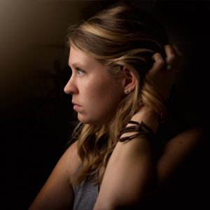 young woman in darkness looking depressed