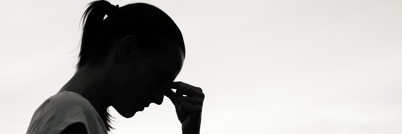 silhouette of the profile of a woman with head bent down and her hand to her temple as in frustration