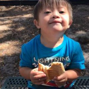 Little boy with Down syndrome wearing a blue shirt and holding a sandwich