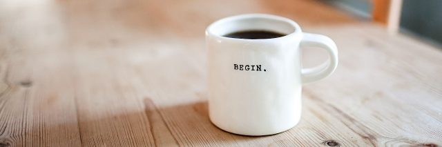 cup of coffee on table with word begin on mug