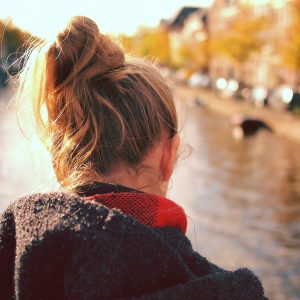 girl looking into canal with hair tied back