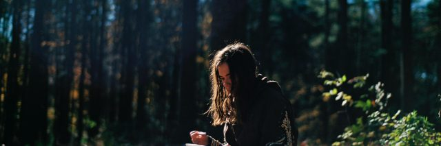 girl in the woods journaling
