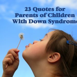 Little girl with Down syndrome blowing dandelion seeds to the wind.
