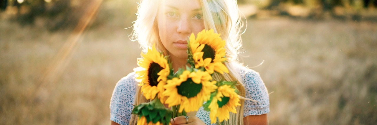 woman with blonde hair holding sunflowers