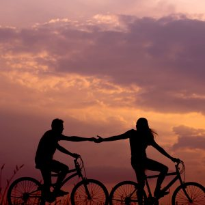 man and woman riding bikes at sunset reaching out to each other romance