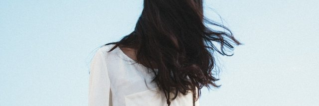 young woman with hair covering face against sky backdrop