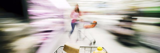shopping cart in grocery store with blurry surroundings
