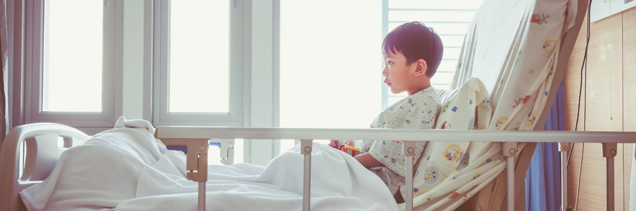 Side shot of a boy sitting on his hospital bed