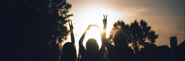 friends silhouetted against sunset with peace and heart signs
