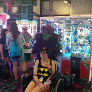 girl in batman shirt in wheelchair with person wearing mask standing behind her at arcade