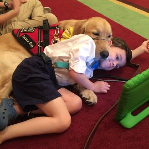 The author's son Kai and Tornado his service dog lying on the carpeted floor, watching an iPad