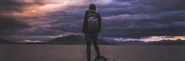 young woman standing in front of stormy sky