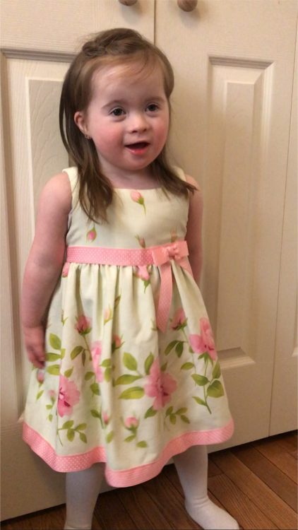 Little girl with Down syndrome standing in front of a white door wearing an Easter dress