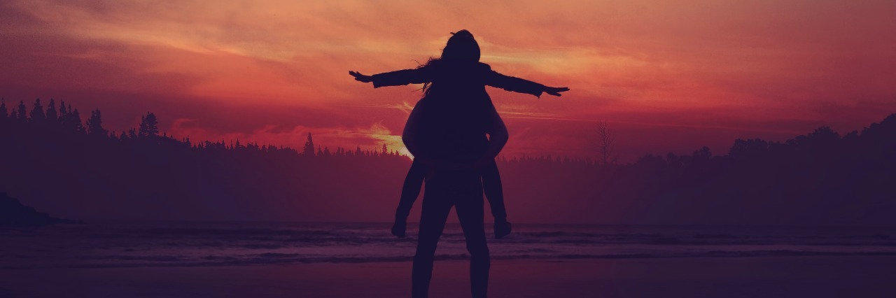 two people standing in water at sunset with one on the other's shoulders, arms spread wide