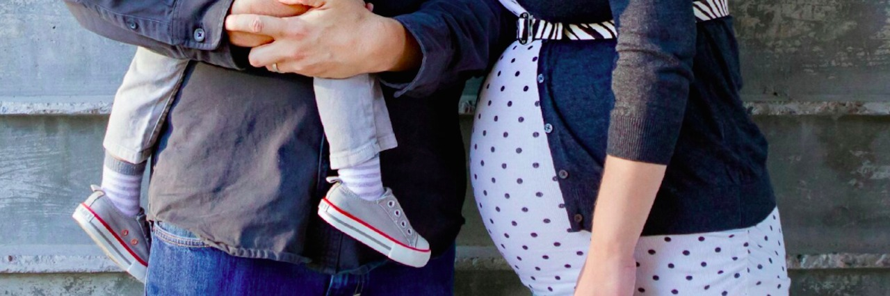 Photo of dad holding child and pregnant mom standing next to them