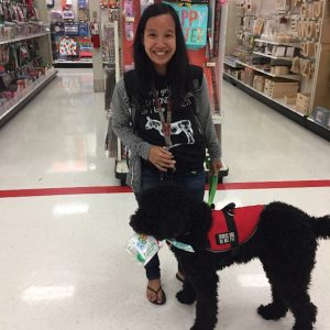 Sara with her service dog Rufus in front of a store aisle