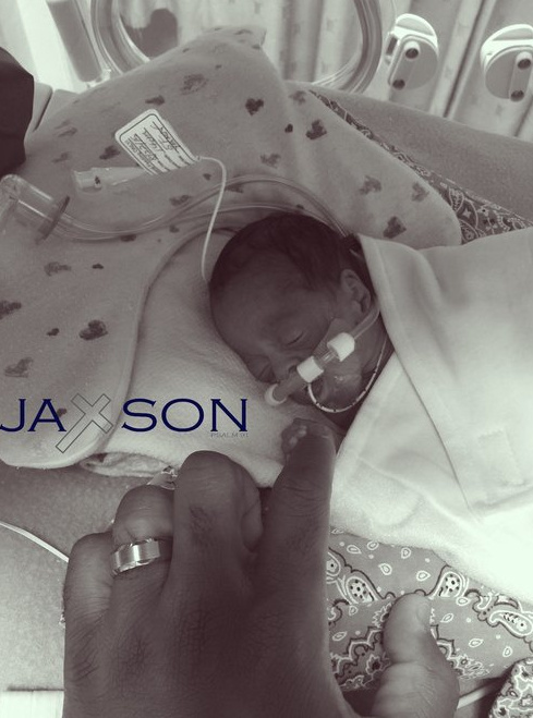 A black and white photo of baby Jaxson in the NICU with his hand around his parent's finger