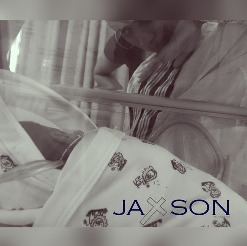 Black and white photo of baby Jaxson in the NICU with his mom looking down at him