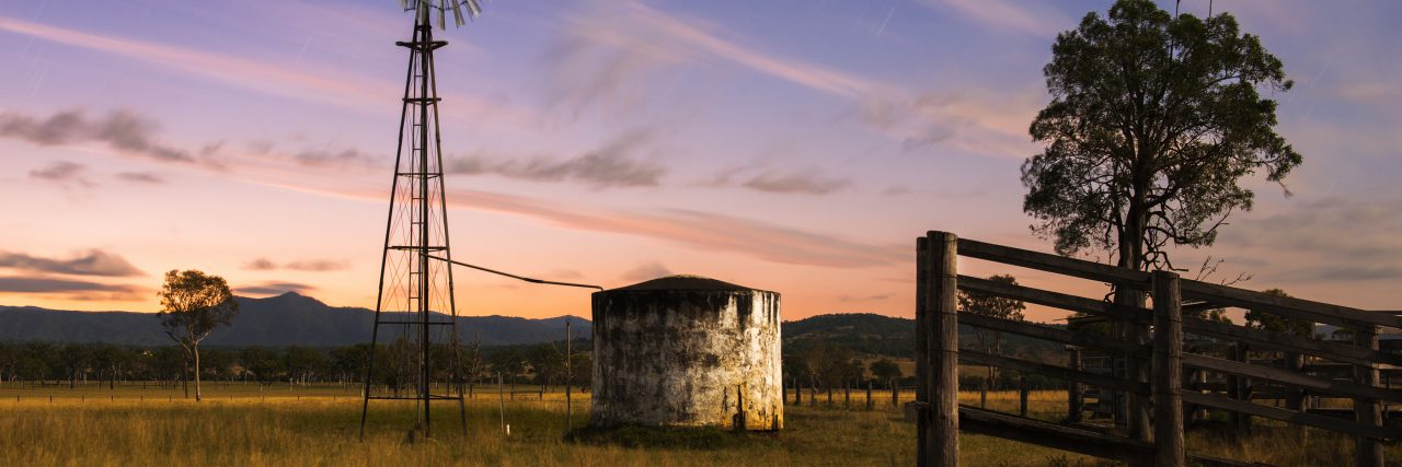 Rural landscape. A fence, a windmill and a silo.
