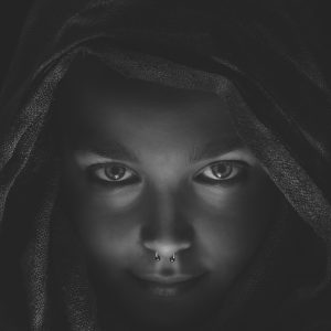 young woman black and white wearing nose ring looking confident at camera