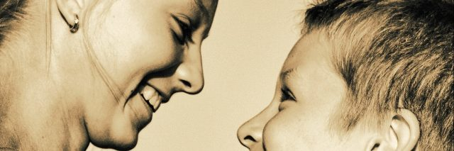 Sepia photo with a profle of sister 9who is older) and brother looking at each other and smiling.